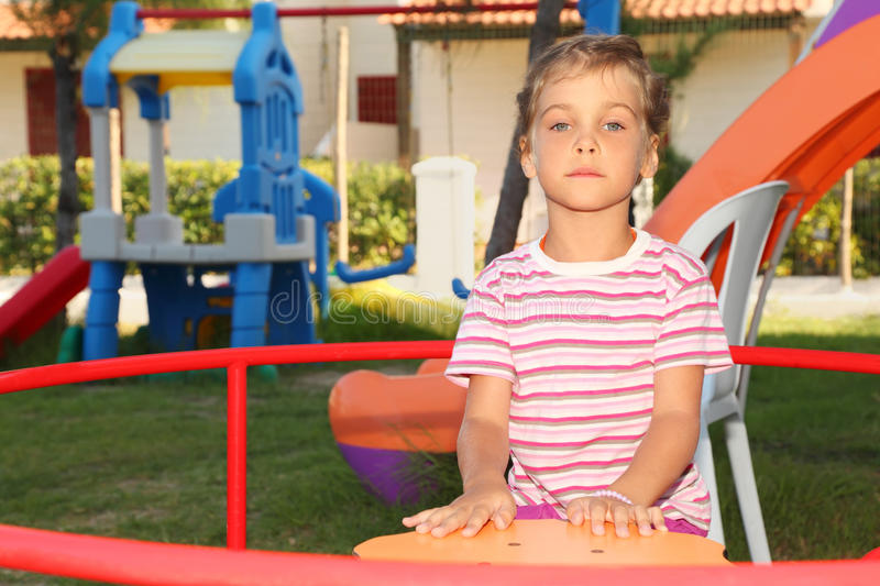 Serious Little Girl Sitting On Merry-go-round Royalty Free Stock Photography