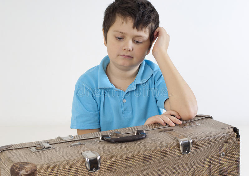 Serious little kid with a suitcase royalty free stock photography