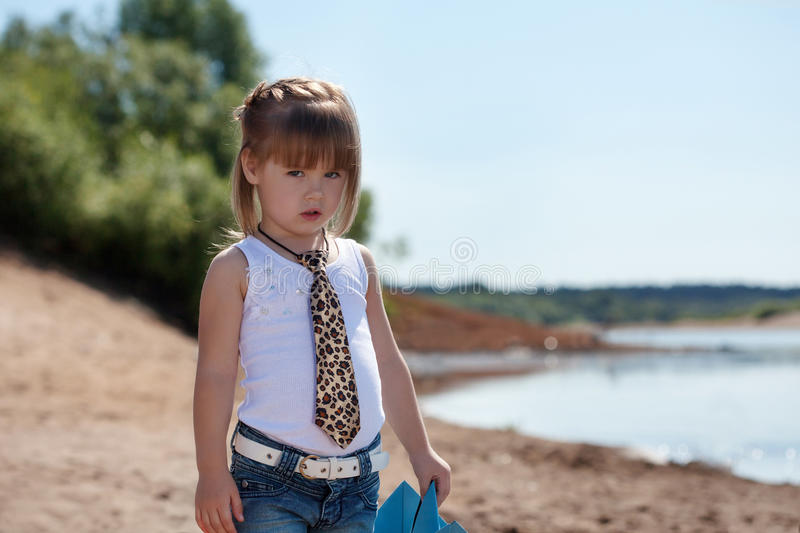 Serious little model posing on lake background. Image of serious little model posing on lake background stock photography