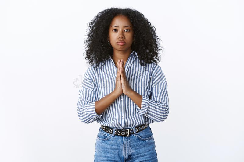 Serious-looking african american troubled girl need help praying holding hands pray supplicating, palms pressed together. Please do favour, begging standing stock images