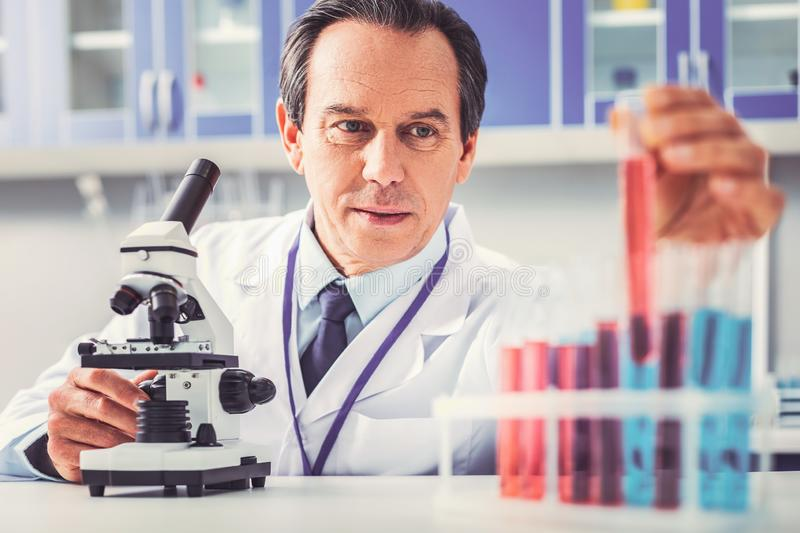 Serious looking biotechnologist feeling concerned. Concerned biotechnologist. Serious looking biotechnologist feeling rather concerned after making prominent royalty free stock photos