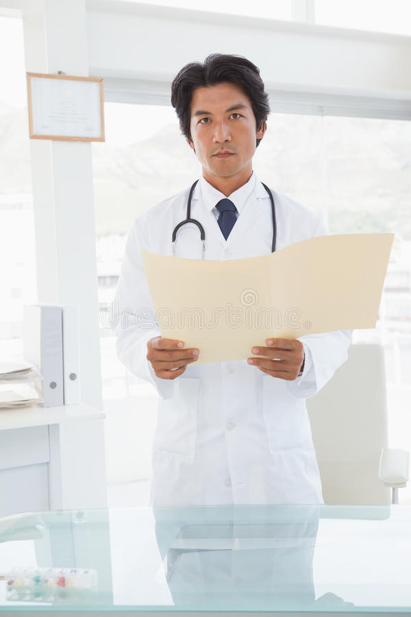 Serious looking doctor with medical files royalty free stock images