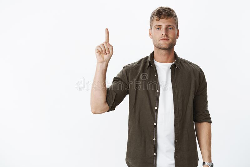 Serious-looking handsome masculine blond guy with blue eyes and bristle making poker face and pointing up with raised stock images