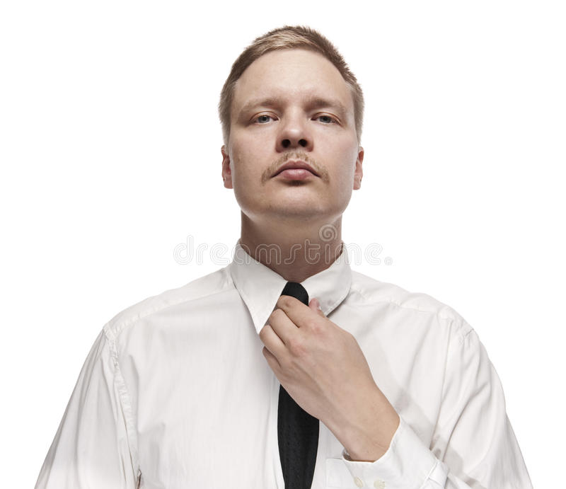 Serious looking man fixing his tie. stock images