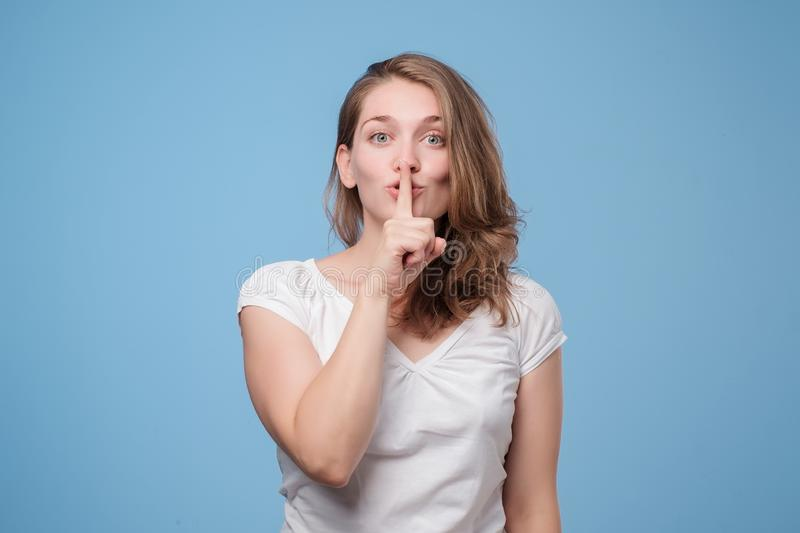 Serious lovely woman asks to keep secret information confidential. Shush, be silent. Serious lovely woman asks to keep secret information confidential stock photos