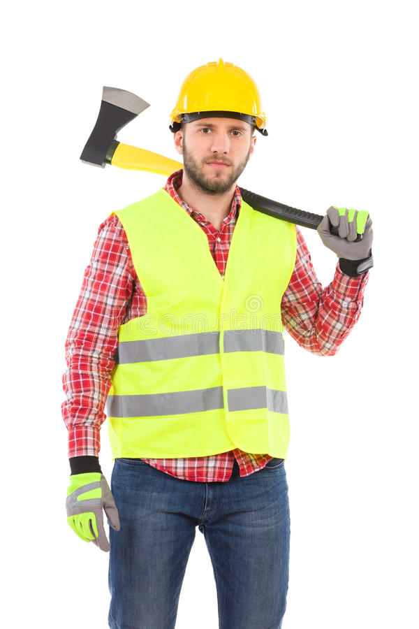 Serious lumberjack with an axe on the shoulder. Serious man in lumberjack shirt, yellow helmet and lime reflective vest holding an axe on his shoulder. Three royalty free stock image