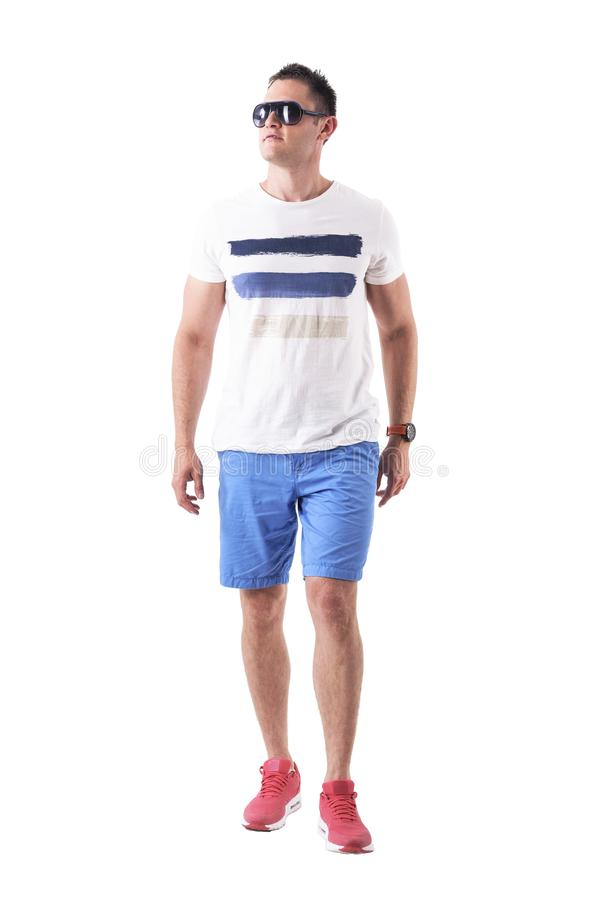 Serious macho man in summer t-shirt and shorts with sunglasses approaching and looking up with attitude. Full body isolated on white background royalty free stock photo