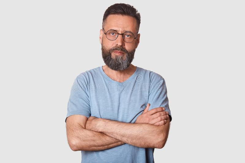 Serious magnetic black haired man posing with folded arms, having strong look, determined facial expression, having athletic arms. Middle aged bearded model stock photography