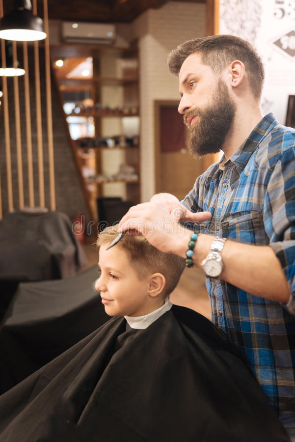 Serious male barber working with a young boy royalty free stock image