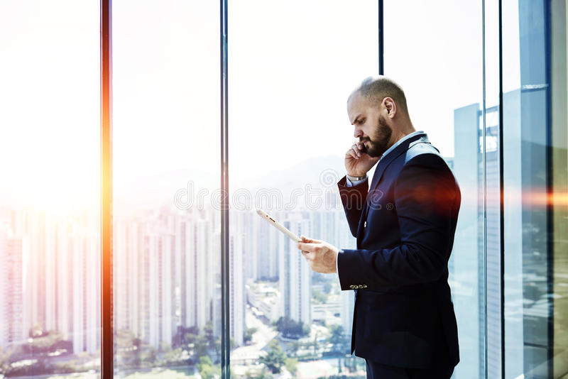 Serious male CEO is talking on cell telephone. Angry businessman is calling via mobile phone to client, while is read on touch pad in e-mail about refusing to stock image
