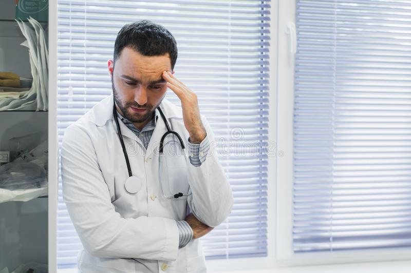 Serious male doctor is holding his stethoscope and standing with arms folded in his office looking at view with menace. stock photo