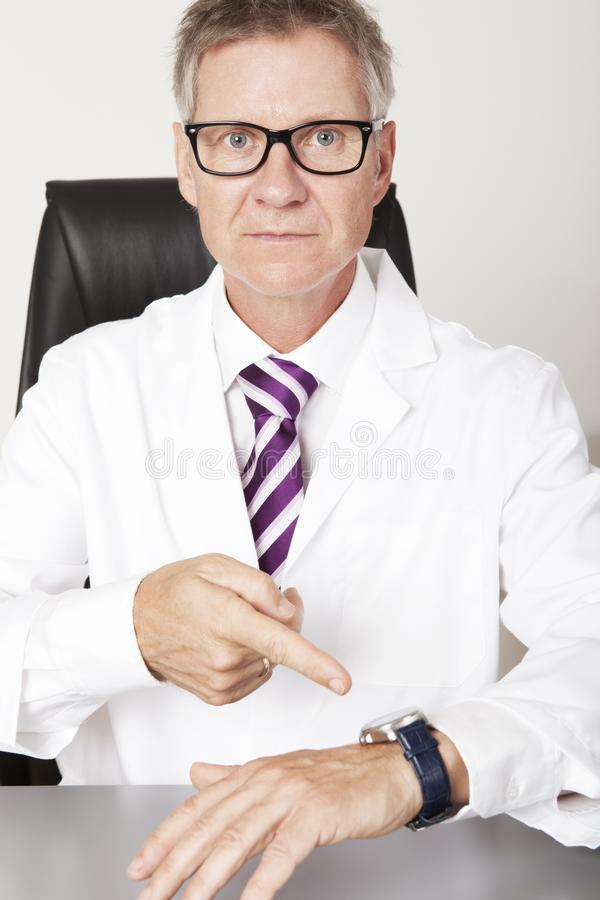 Serious Male Doctor Pointing Wrist Watch royalty free stock photos