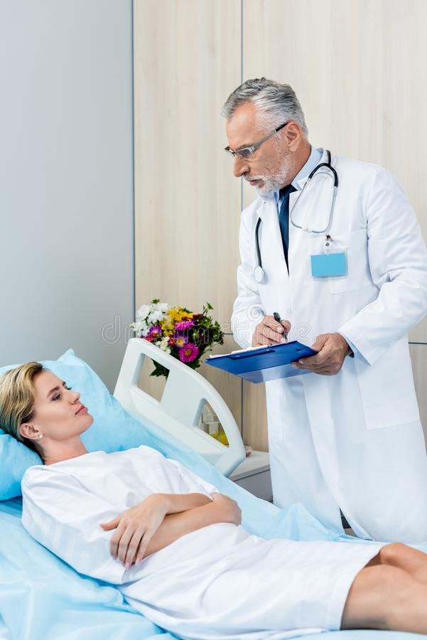 Serious male doctor with stethoscope over neck writing in clipboard near adult female patient in hospital. Room royalty free stock photo