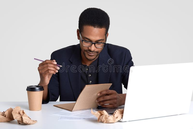 Serious male employee with dark healthy skin, holds pen, writes notes in diary, makes list to do, plans work for next week, makes royalty free stock image