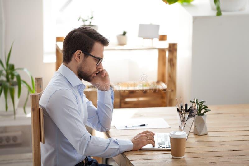 Serious male employee talking on phone using laptop royalty free stock image