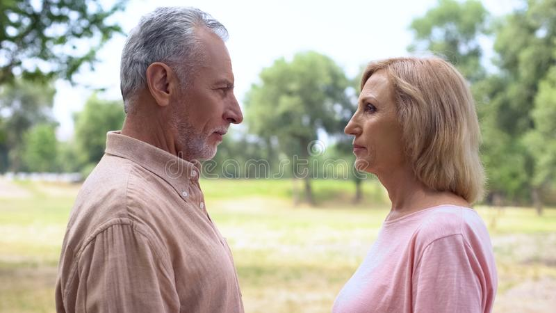 Serious male and female standing in front each other, couple misunderstanding. Stock photo royalty free stock photos