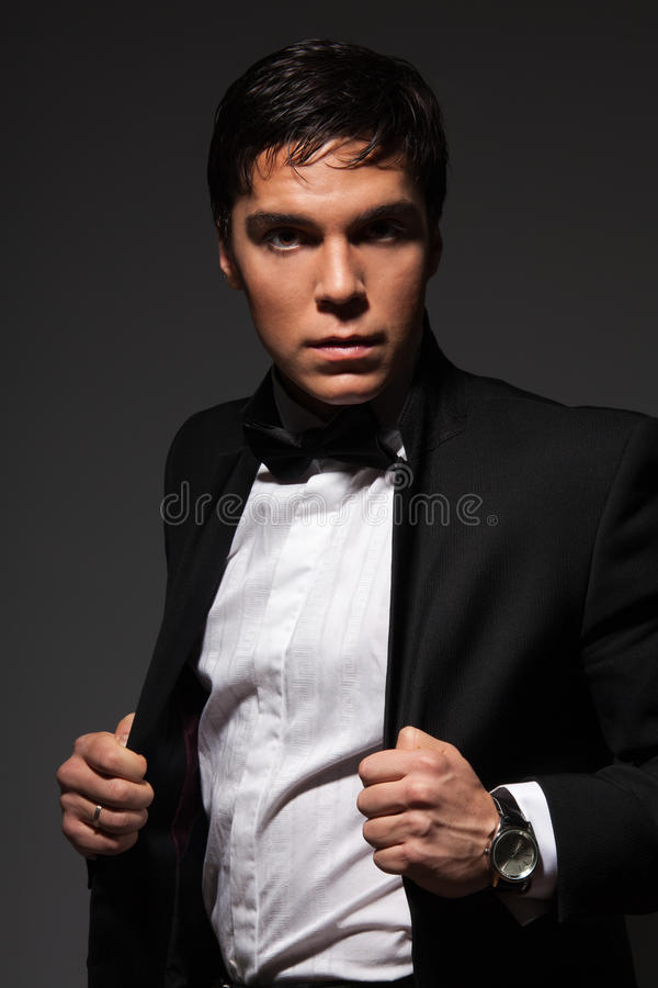Serious male holding his jacket stock photography
