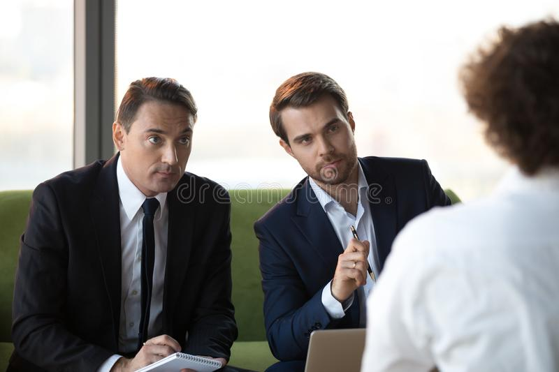 Focused male employers consider applicant candidature at hiring royalty free stock photo