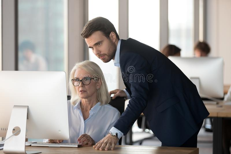 Serious male mentor supervising female employee helping with computer problem. Serious male mentor manager ceo supervising middle aged female employee helping royalty free stock photo