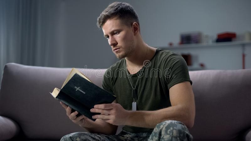 Serious male military reading bible, religion and faith, psychological therapy. Stock photo stock photography