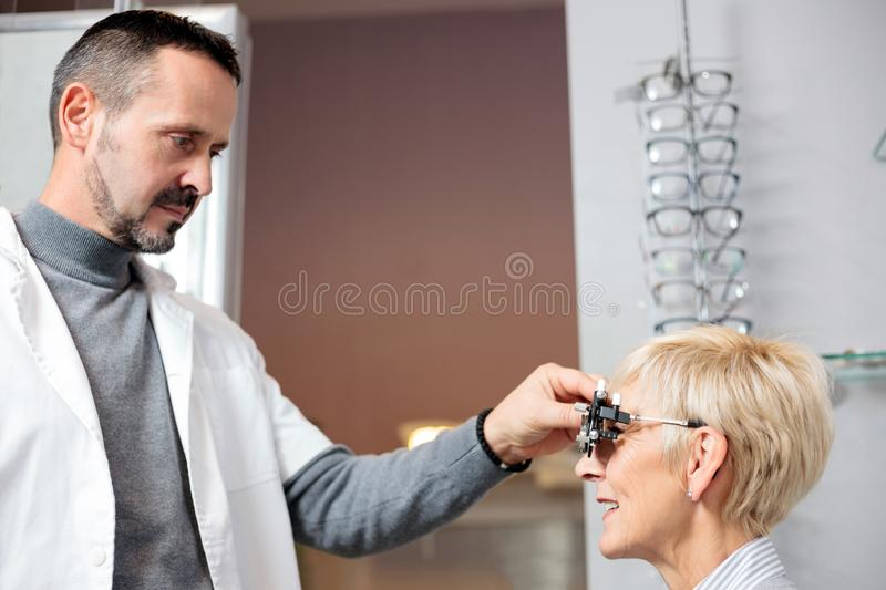 Serious male optometrist examining mature woman, determining diopter in ophthalmology clinic stock image