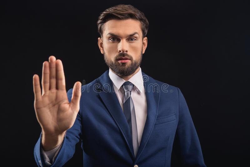 Serious male politician swearing in his innocence. I swear. Confident young businessman is standing and stretching hand forward. on black background stock photos