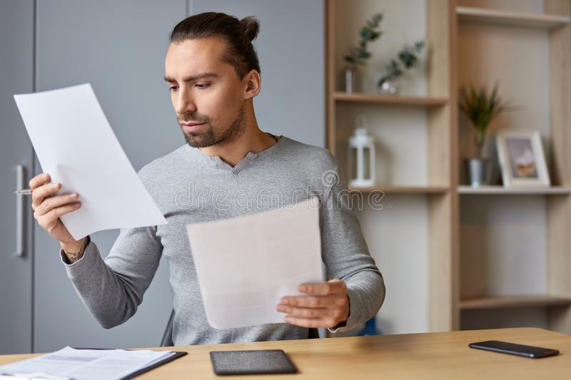 Serious male reading financial documents at home. Handsome adult man examining taxes data on financial papers while sitting at table at home royalty free stock images