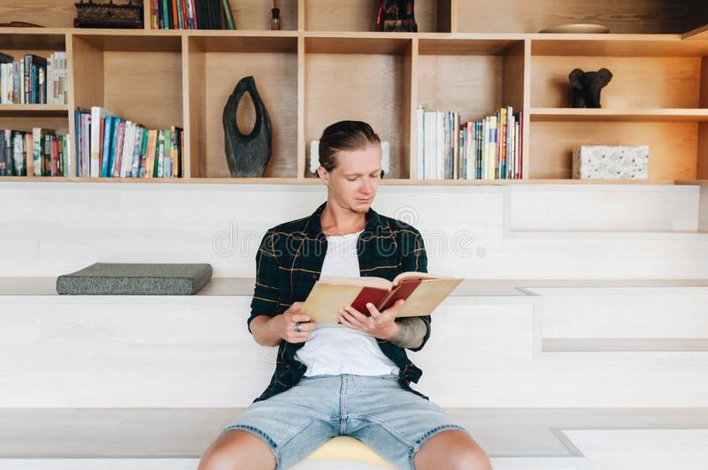 Serious male student reading a book in a library royalty free stock photography