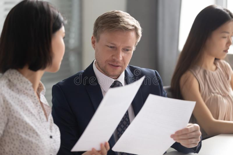 Serious team leader reviewing financial report with asian female coworker. royalty free stock photo
