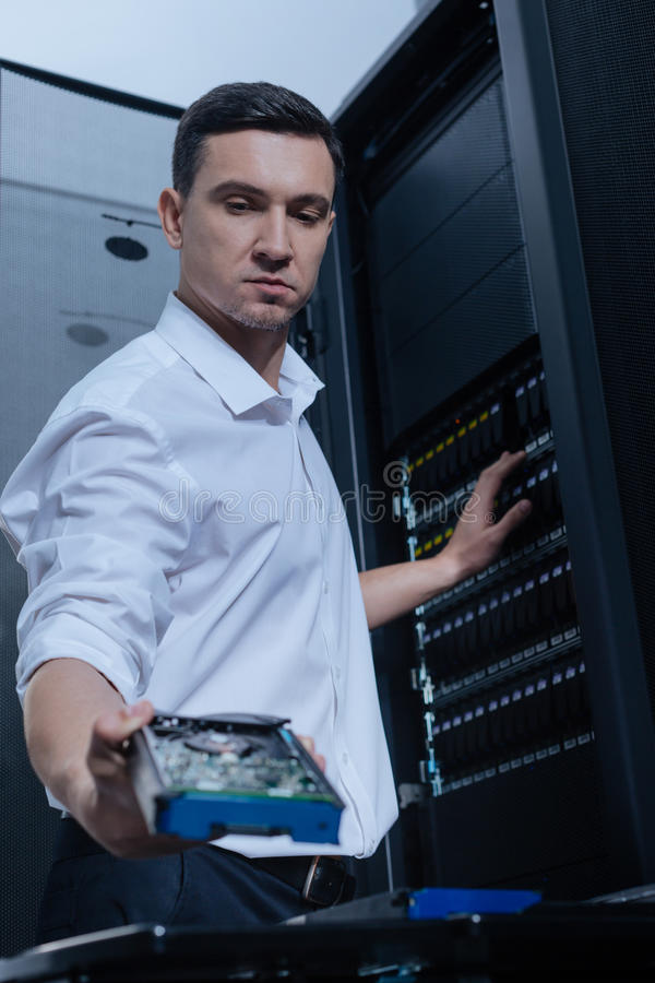 Serious male technician working with the network server royalty free stock photo
