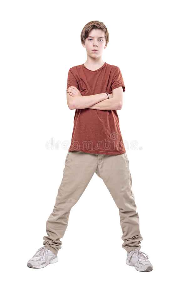 Serious male teenager standing with crossed arms stock image
