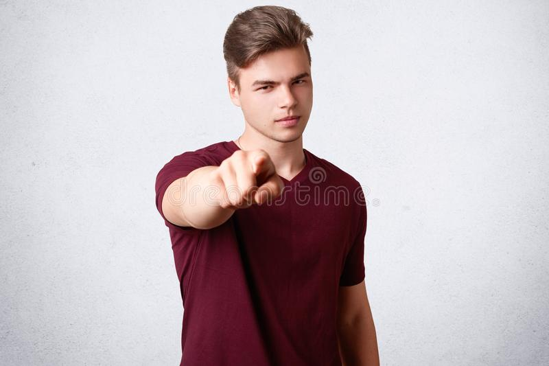 Serious male with trendy hairstyle, dressed in casual t shirt, points with fore finger directly at camera, chooses you, poses agai stock photography