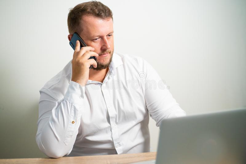 Serious male in white shirt talking on the phone in the workplace sitting at a table near the computer.  stock photo