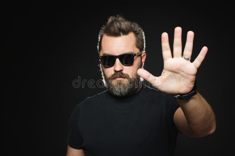 Serious man with beard in a black shirt and sunglasses on a black background in studio. Confident guy standing in front of camera royalty free stock image