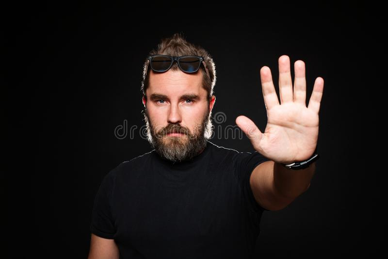 Serious man with beard in a black shirt and sunglasses on a black background in studio. Confident guy standing in front of camera stock photos