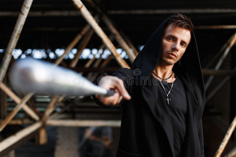 Serious man in black clothes with a hood holds a bat. Serious man in black clothes with a hood holds a bat royalty free stock photography