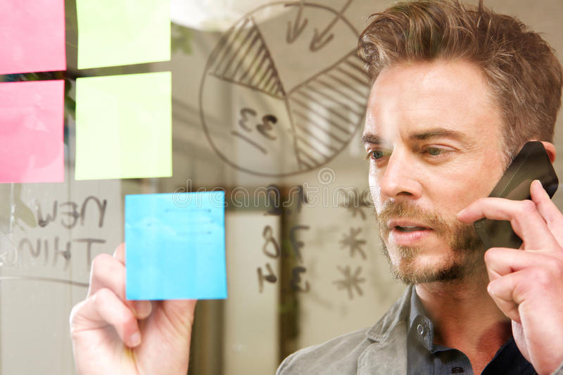 Serious man on business call with transparent idea board. Portrait of serious man on business call with transparent idea board stock photos