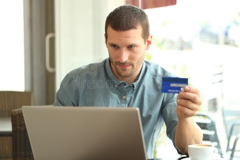 Serious man buying with credit card and laptop in a bar. Serious man buying with credit card and laptop sitting in a coffee shop stock photo