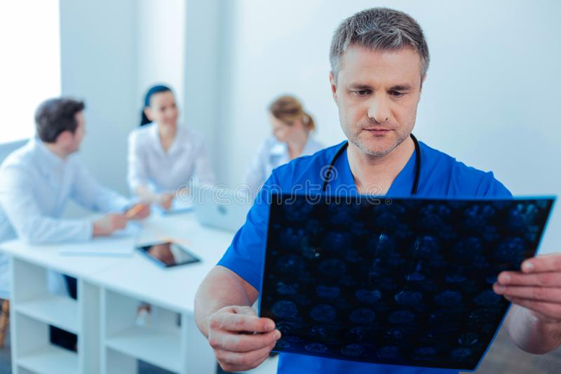Serious man doing roentgen examination. Need to concentrate. Handsome doctor pressing lips and wrinkling forehead while looking at picture royalty free stock photos