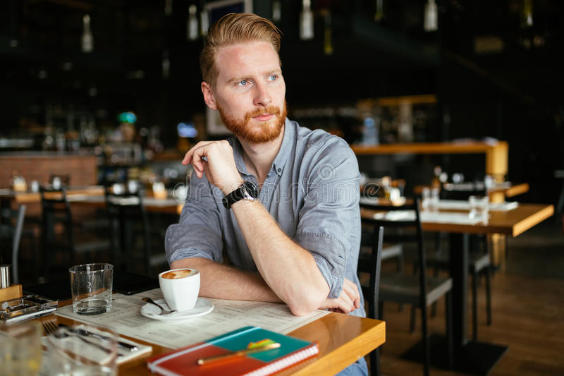 Serious man drinking coffee stock images