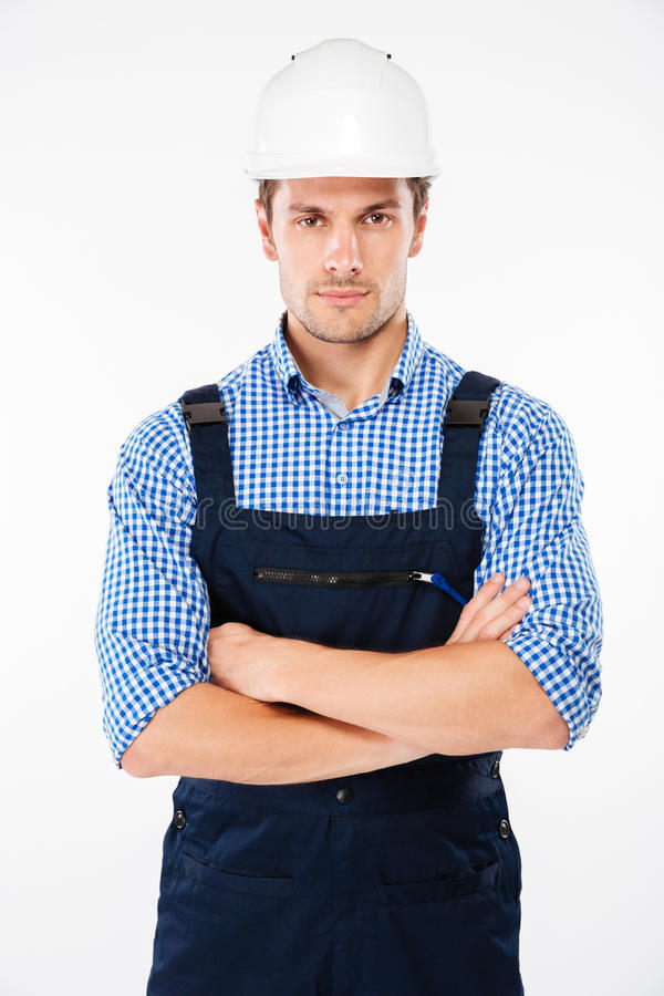 Serious man foreman in hard hat standing with handsom folded stock image