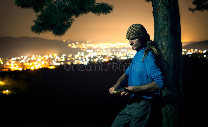 Serious man in the forest at night with a knife. Serious man in the forest with a knife cutting wood against city lights stock photo