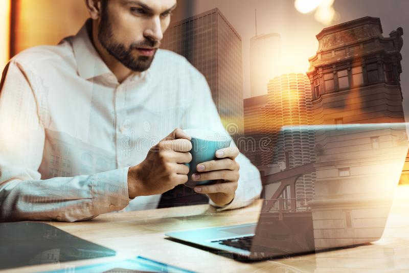 Serious man holding coffee cup and staring at laptop screen stock images