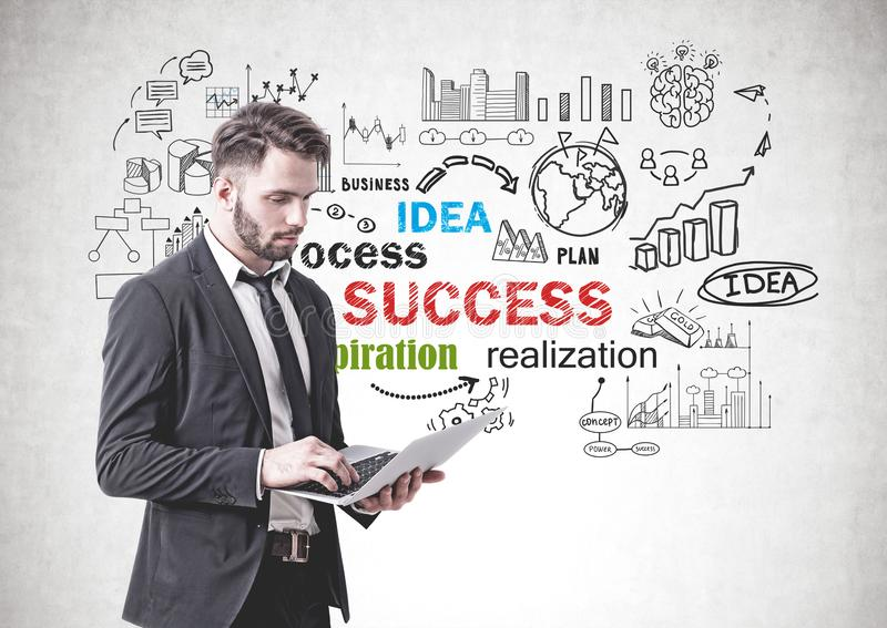 Serious man with laptop, business success. Serious bearded businessman working with laptop standing near concrete wall with business success sketch drawn on it stock images