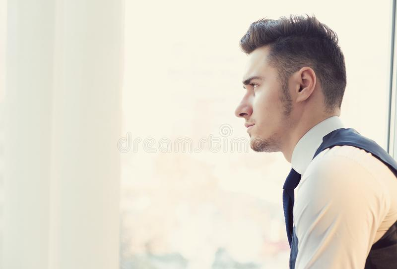Serious man looking away in window royalty free stock image