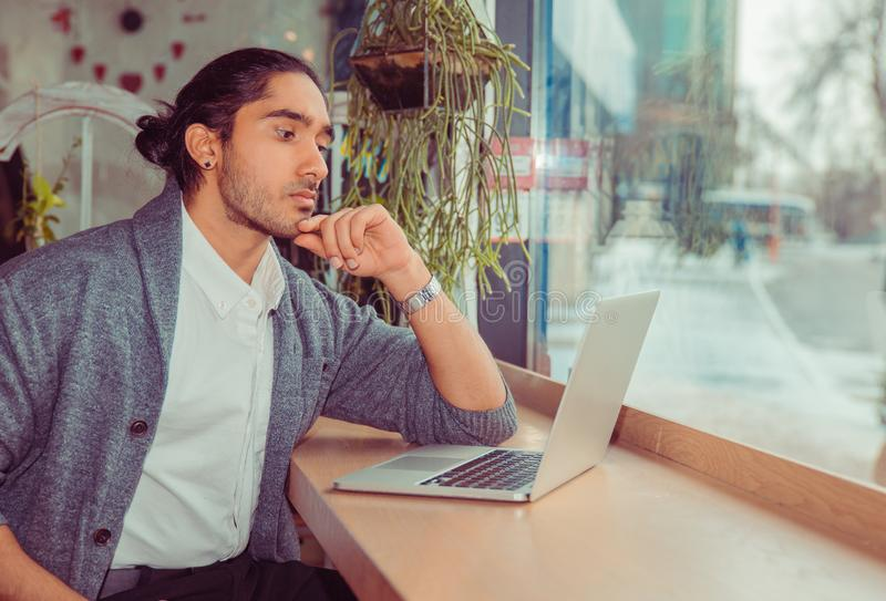 Serious man looking at computer. Businessman at work. Closeup portrait of a handsome guy wearing white shirt, gray blouse sitting near window at table in stock photography