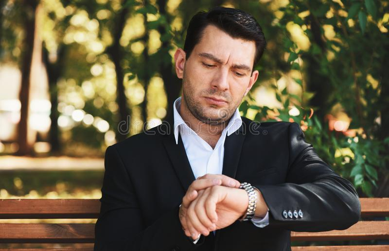 Serious man looking on his watch in the park royalty free stock image