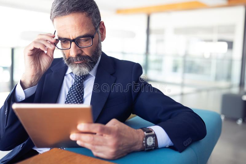 Serious man managing director of big prosperous company is holding touch pad. Serious man managing director of prosperous company is holding touch pad royalty free stock photo