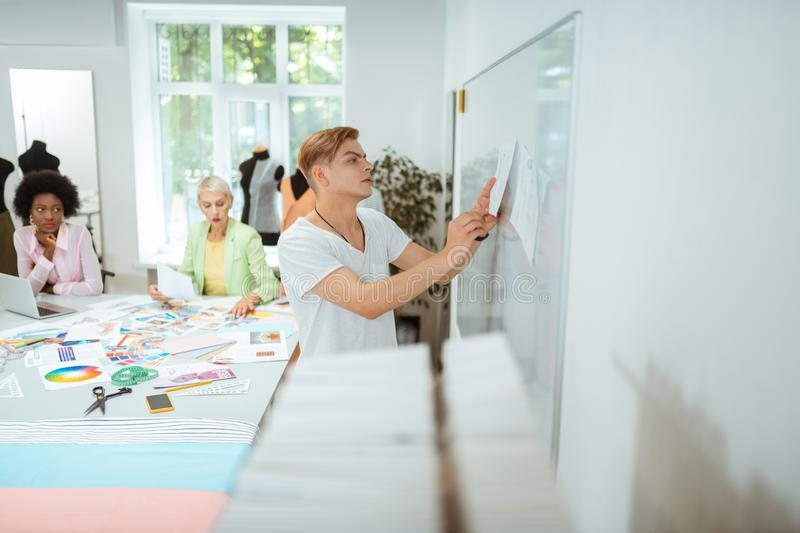 Serious man pinning a sketch on the whiteboard royalty free stock images