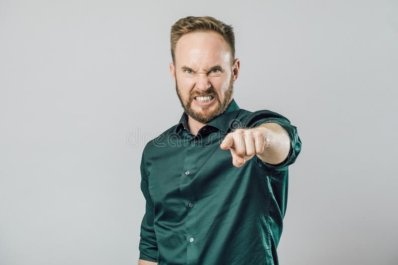 Serious man pointing at camera. Isolated on gray royalty free stock image
